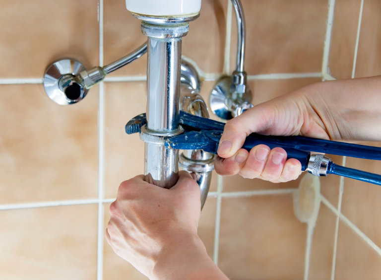 hands of plumber with sink and wrench