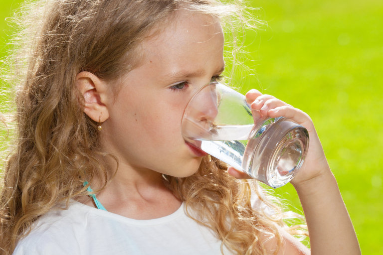 girl drinking glass of water outdoors