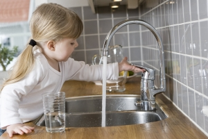 small girl in kitchen drinking water