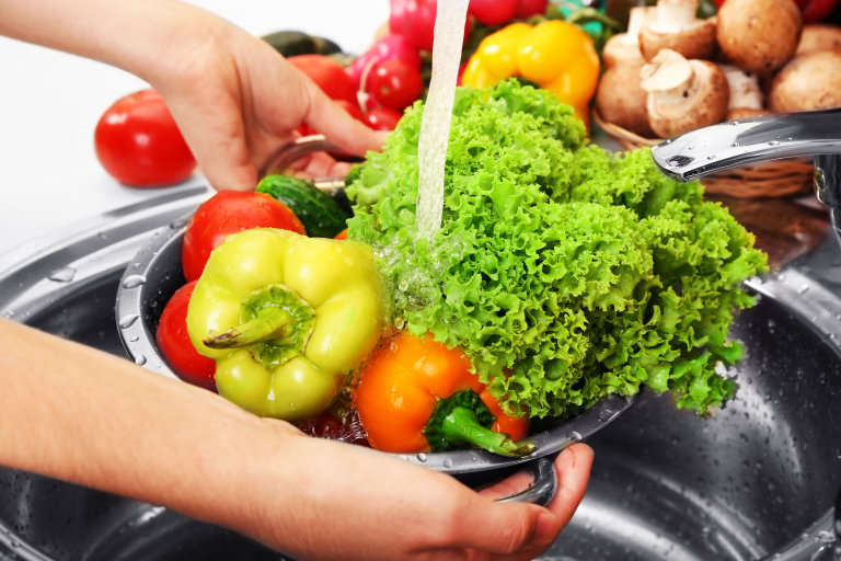 woman washing vegetables in sink