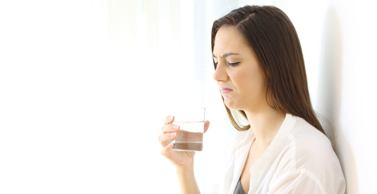 disgusted woman drinking water with bad taste