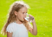 child drinking glass of water outdoors